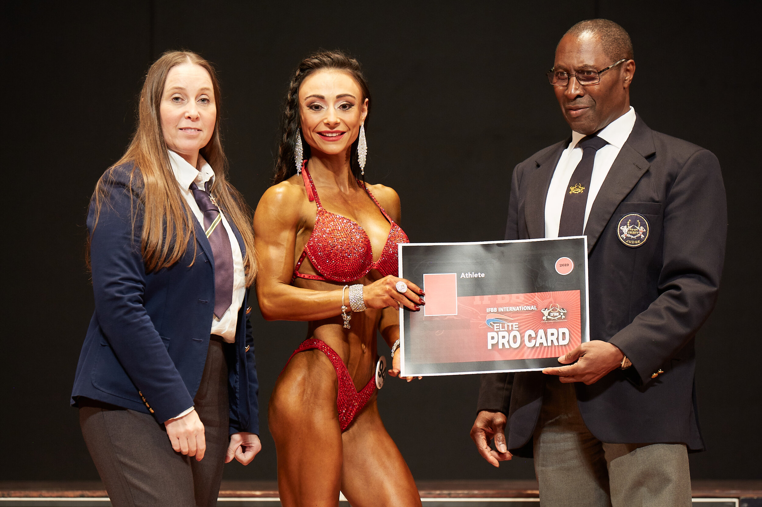 Chloe Greenwood receives her IFBB Elite Pro card after winning bodyfitness overall.