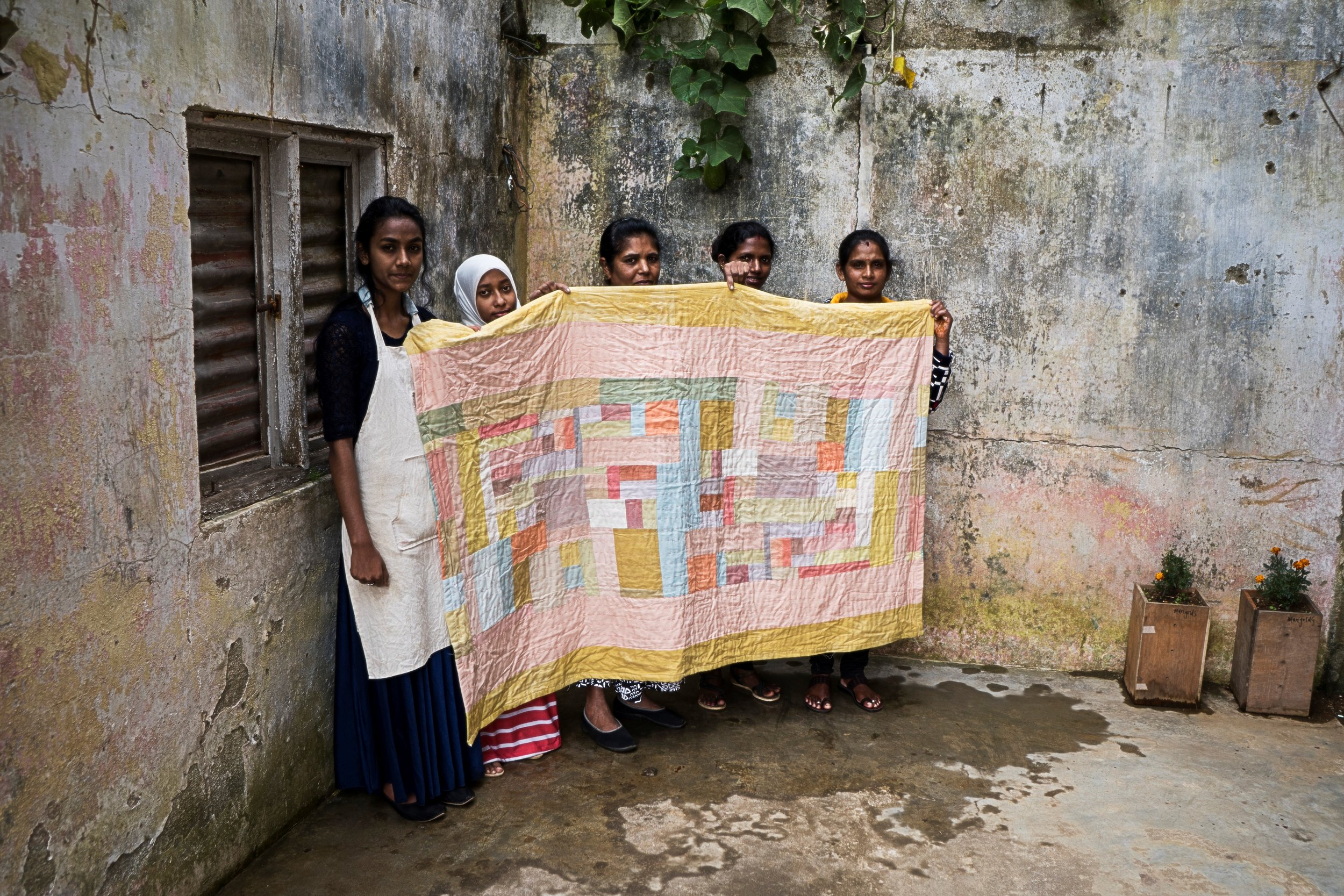The AMMA crew showing one of their signature pieces – a patched blanket.  Photo: Maria Lundin Osvalds