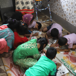 Children color pictures at the Hope for Life drop-in center
