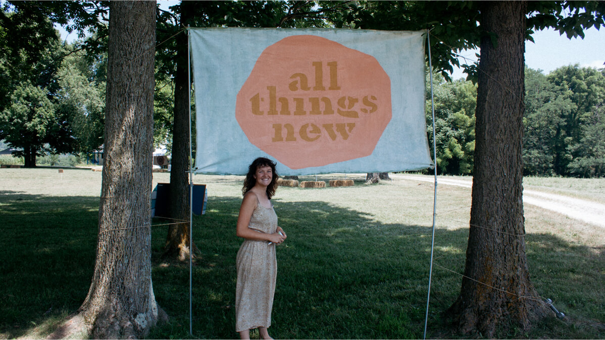 Lyric Morris-Latchaw in front of the banner she for All Thing New Festival.