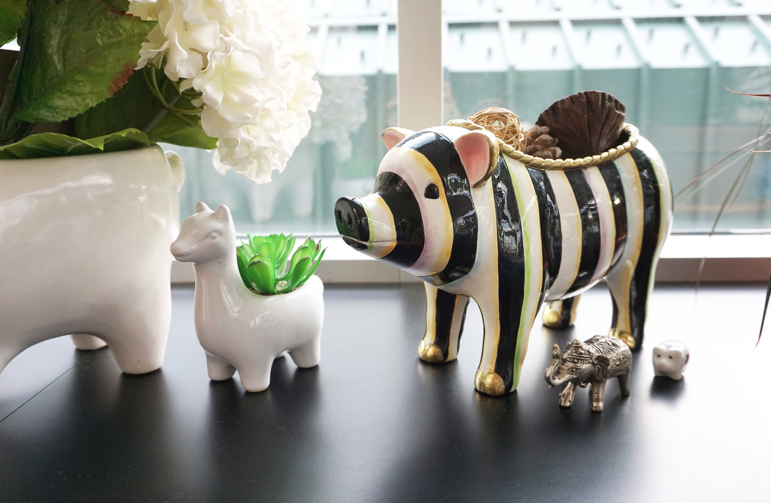 I love decor with animal faces. This piggie is from Mackenzie Childs and the two llamas are from West Elm.