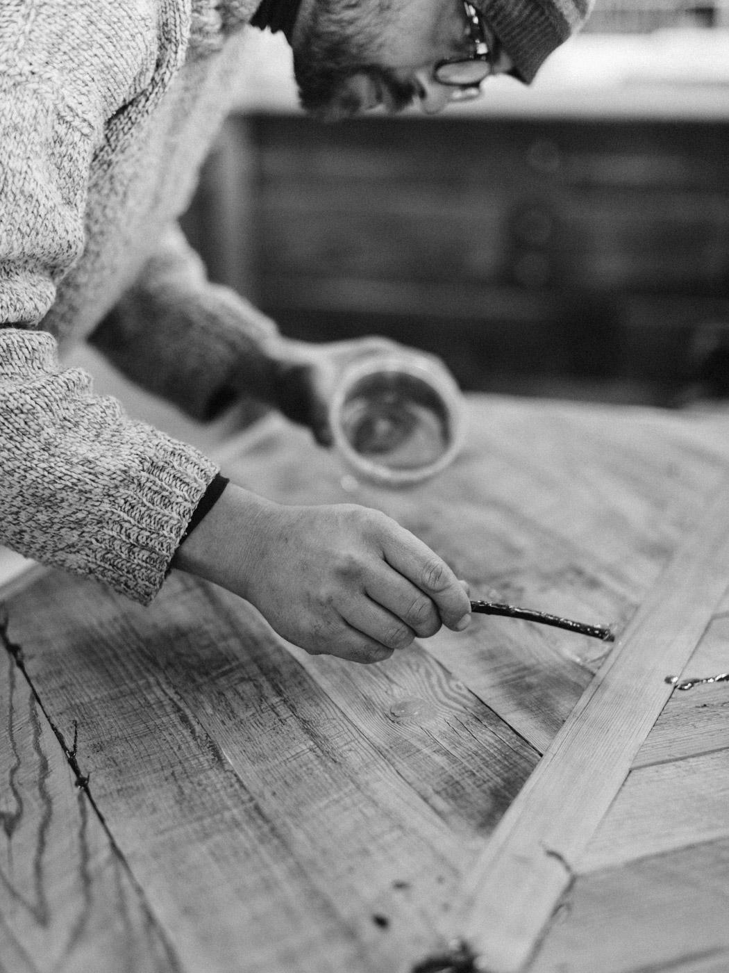 BeReclaimed - Reclaimed Wood Table - Brown Barnboard - Black and White - Bernard Applying Epoxy.jpg