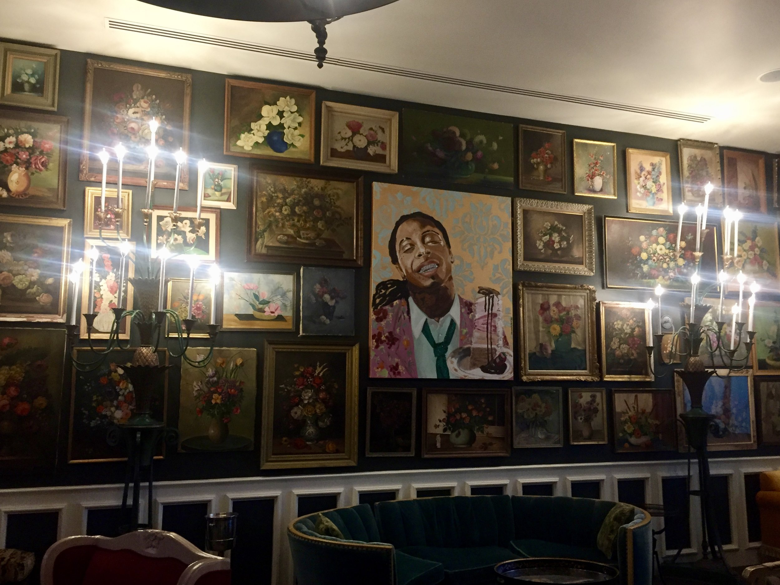 Lil Wayne amid a sea of paintings in the Hotel Pontchartrain. Artist is Ashley Longshore.