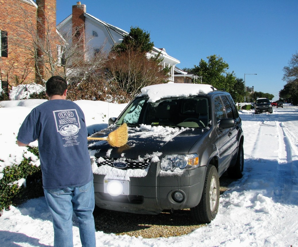 Male Nojacketus  sweeping the snow off a car in Virginia Beach. Circa 2016.