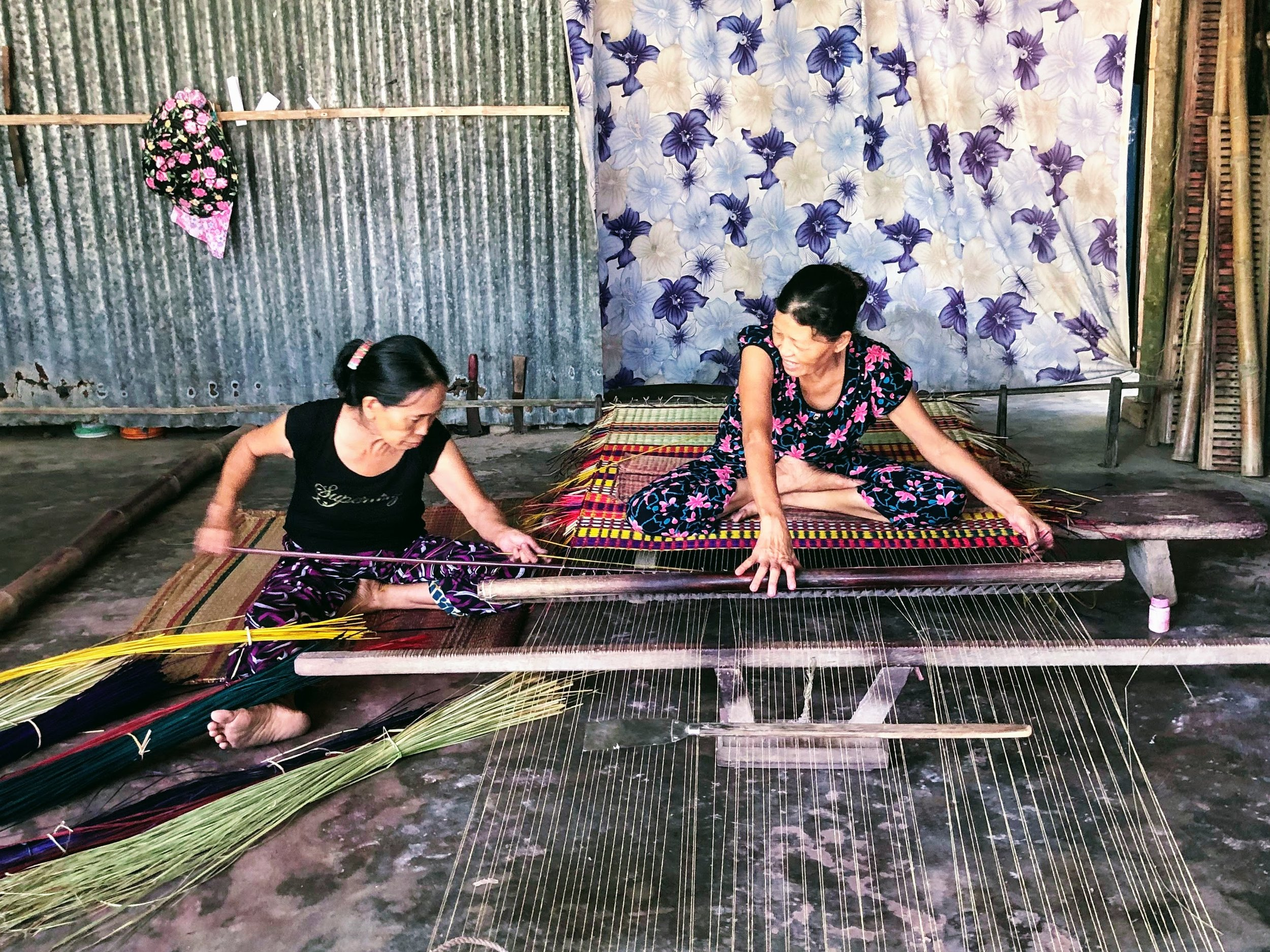These women are weaving grass mats. It takes them 3-4 hours to complete one. They make about $1 profit on each. The woman on the left is 66. She's been weaving mats in this open-air room for the past 50 years.