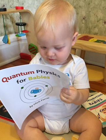 """Here's my son at a little over 1 year old, learning how to """"ThinkQuantum"""". Needless to say it's never too early to start learning quantum physics … thankfully it's also never too late. The book he's reading is one of many fantastic books by  Chris Ferrie ."""