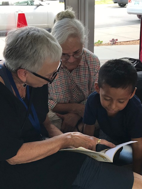 Two Christ Church Cathedral parishioners reading to a child at the bus station.