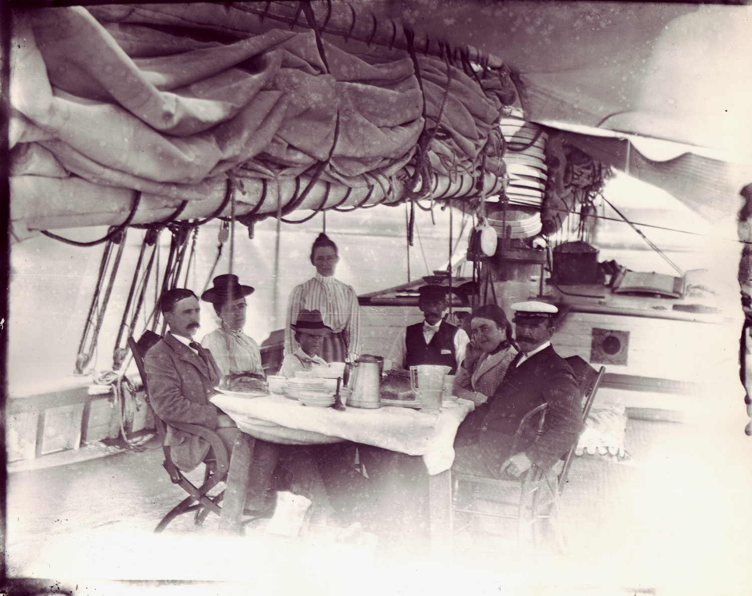 A well-to-do family enjoying a summer aboard the Taber, sailing the waters between Long Island and Newport, circa 1901.