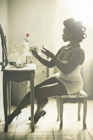 Black and White photo of a black woman in pin up with rollers in her hair sitting infront of a mirror and spraying perfume on her self.