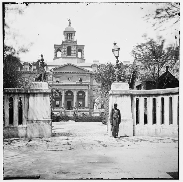 A Union soldier stands guard outside of the Orphan House, which was used as a Union hospital during the Civil War. Note the statue of William Pitt inside the wall, which was displayed at this location from 1808-1881. Charleston, SC Orphan Asylum, 1865. Civil War Photograph Collection, LOC.