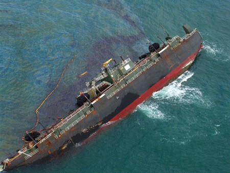 The disabled vessel, the T/B DBL 152, discharges oil into the Gulf of Mexico in 2005. Image credit: ENTRIX, Inc.
