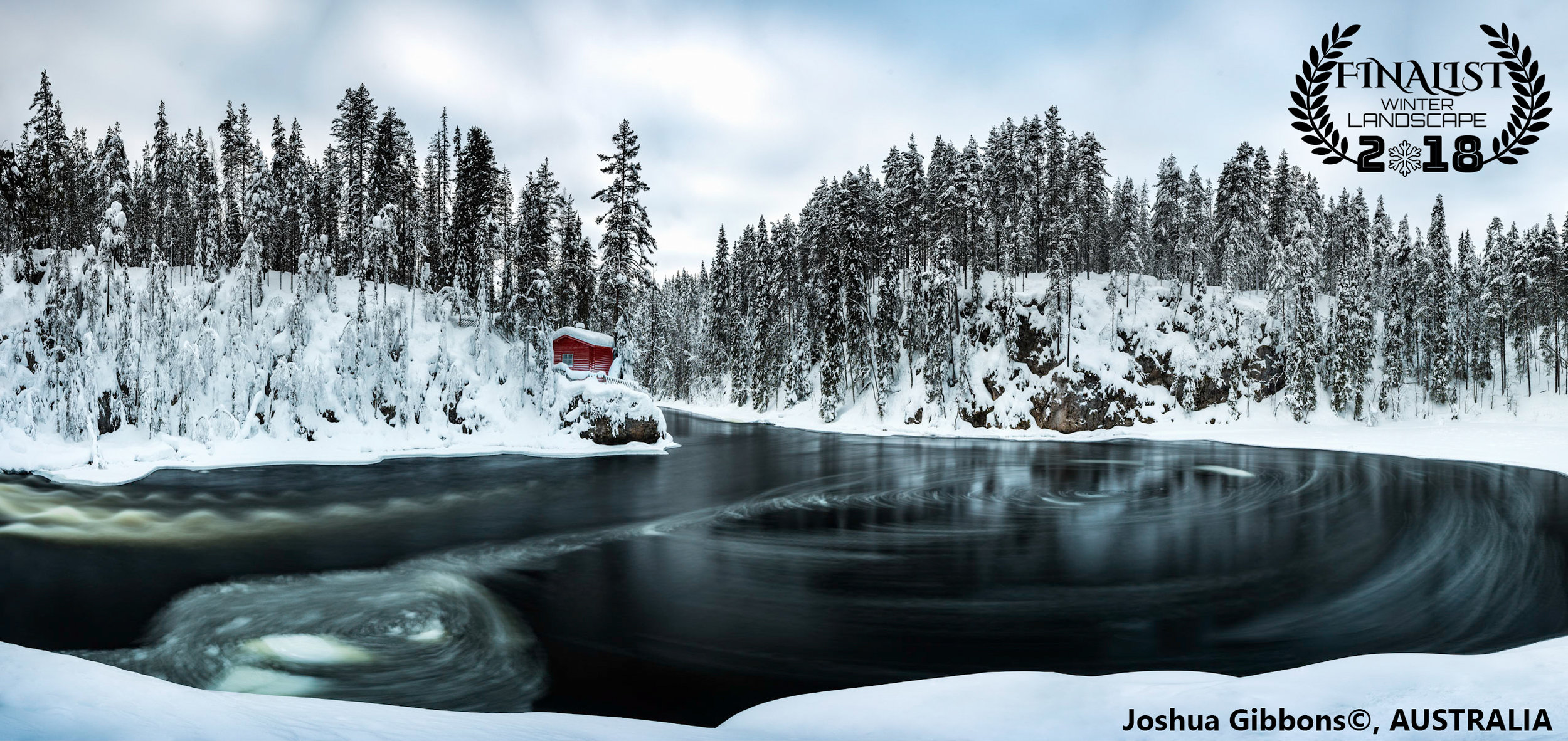 """'Isolation'  """"A traditional log cabin sits in solitude on the Kitkajoki River, Finland. The unique shape of the riverbend causes ice to swirl and spiral its way through the frozen forest.""""  Photographer: Joshua Gibbons, AUSTRALIA"""
