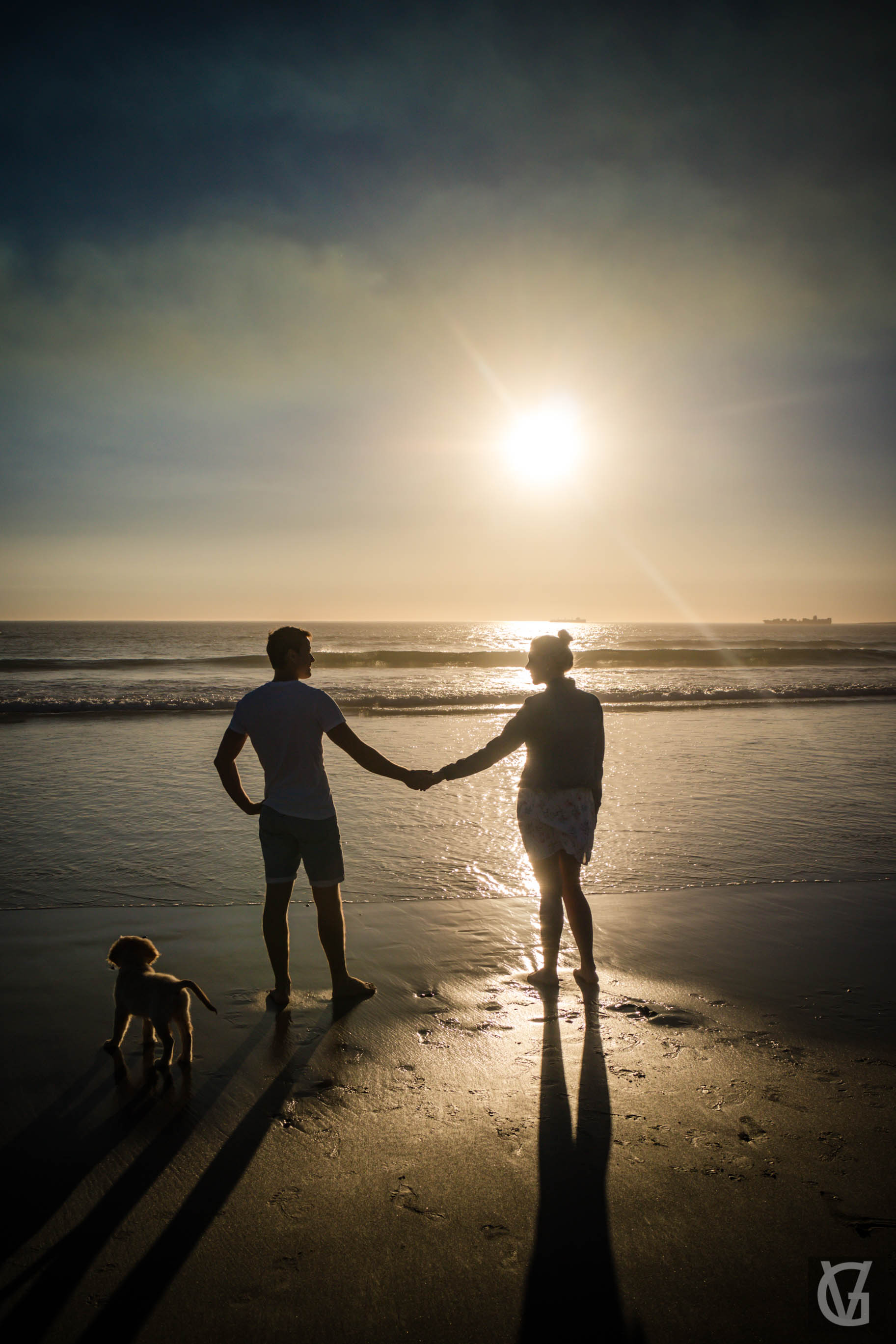 An engaged couple hold hands looking into the sunset