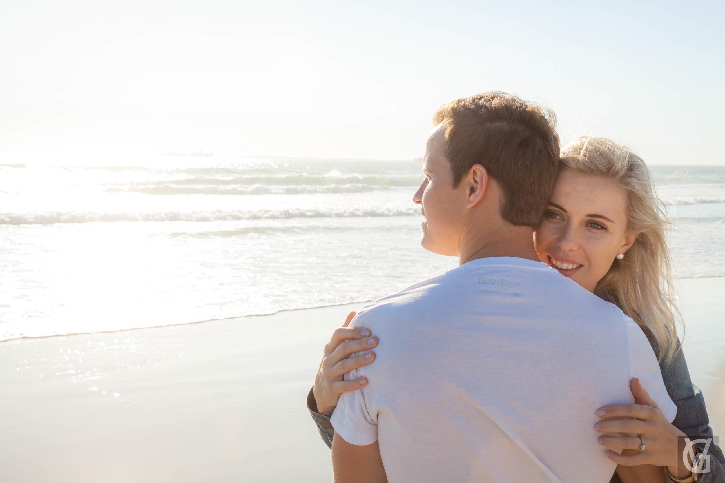 An engaged couple share a hug on the beach at sunset