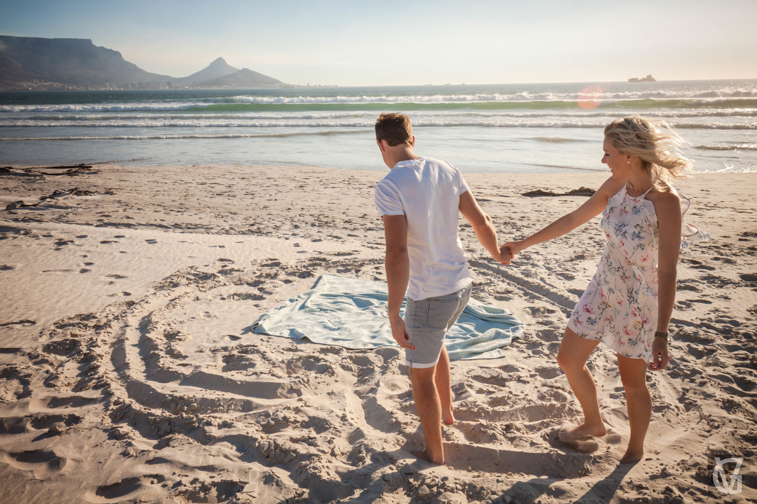An engaged couple draw a heart in the sand together on a beach