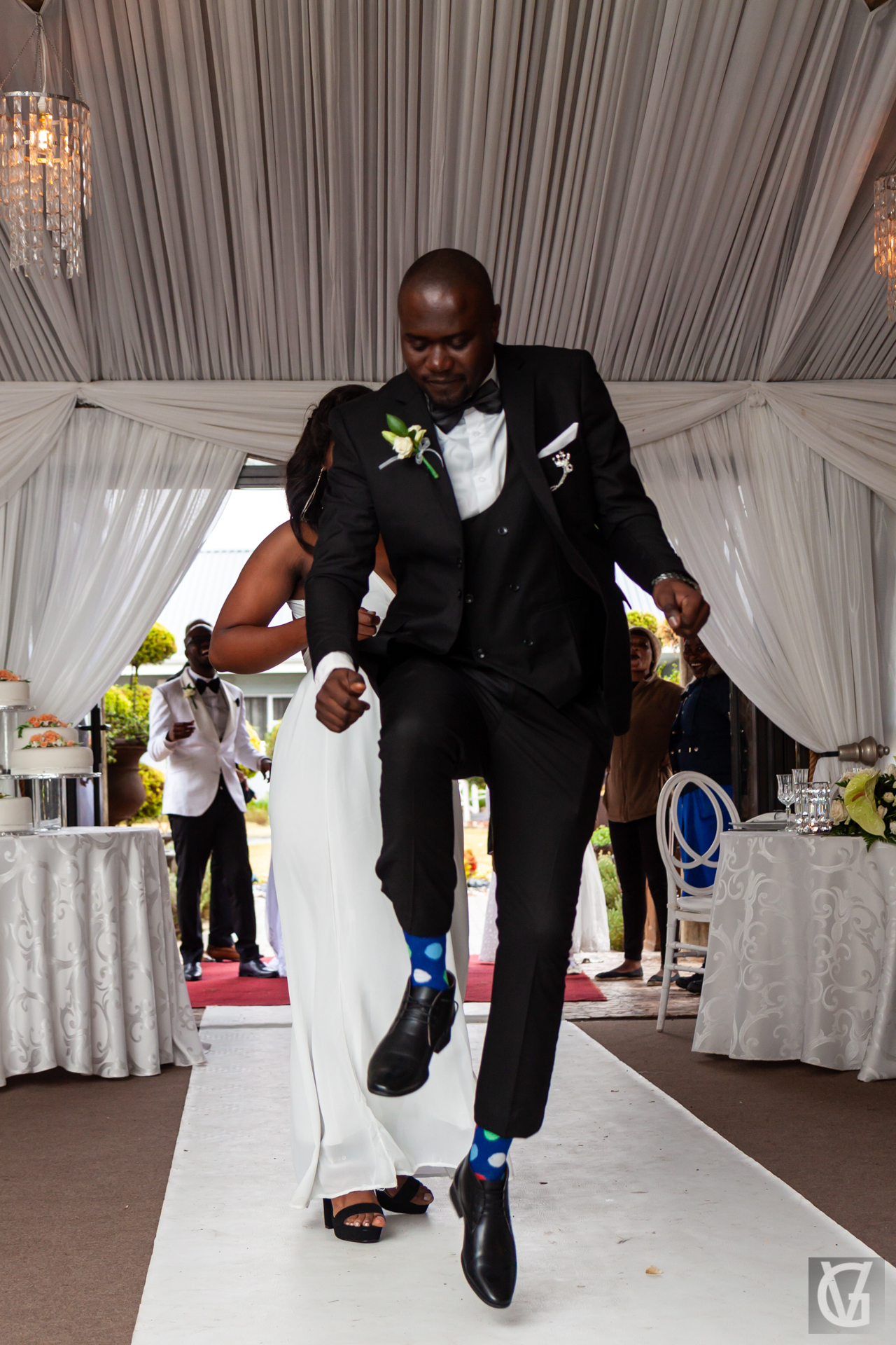 A man jumping and dancing while entering a wedding reception