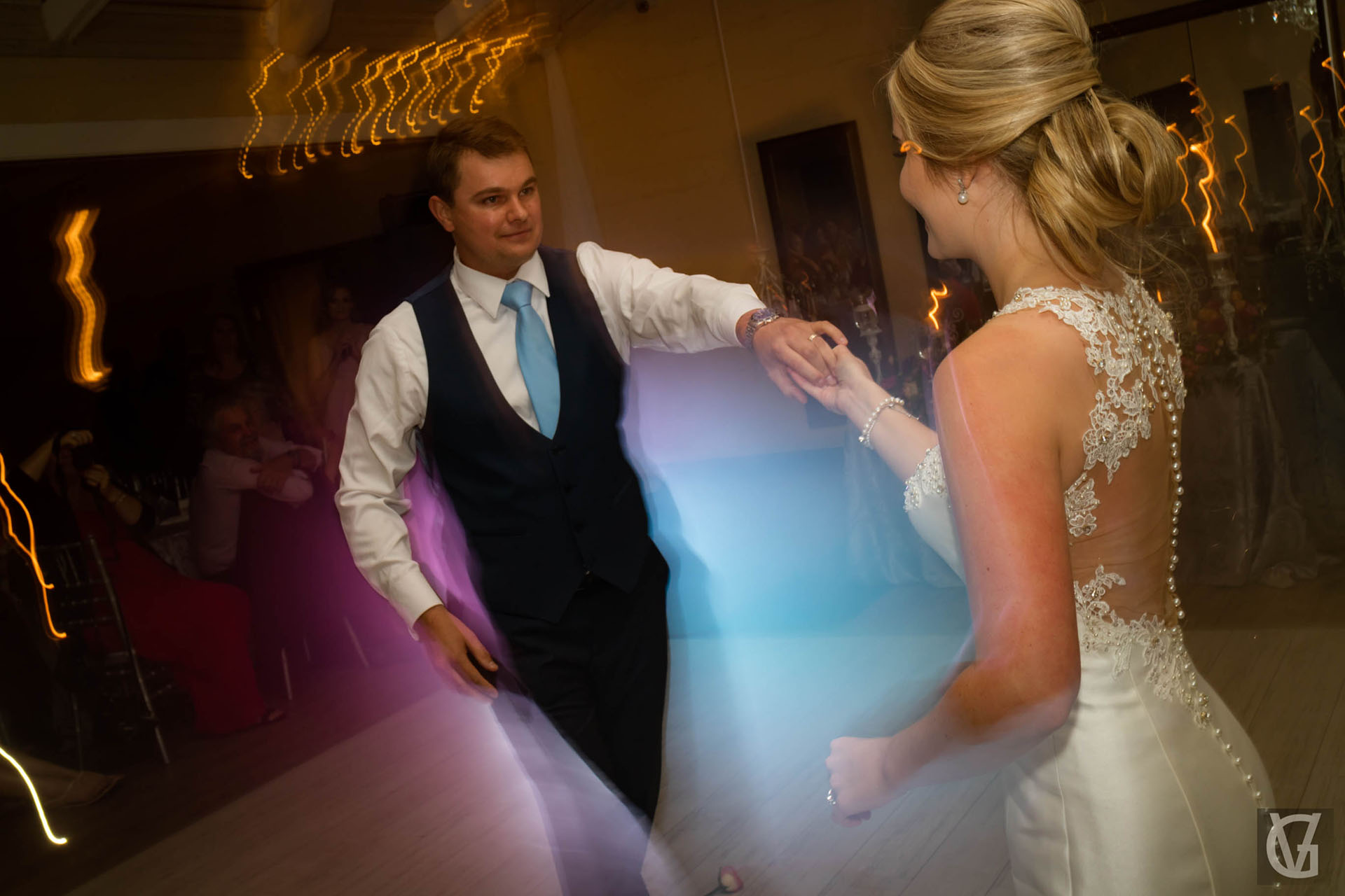 A newlywed couple dancing their first dance together with lights and a fog machine