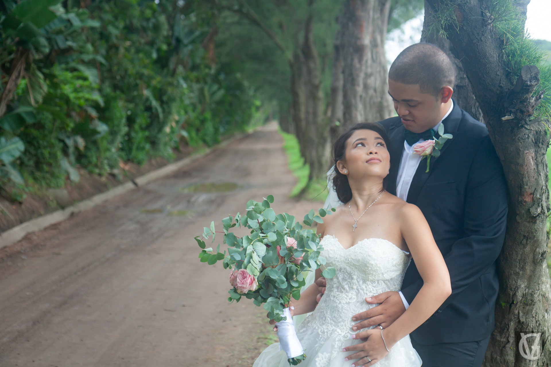A newlywed couple standing by a row of trees at the Durban Country Club