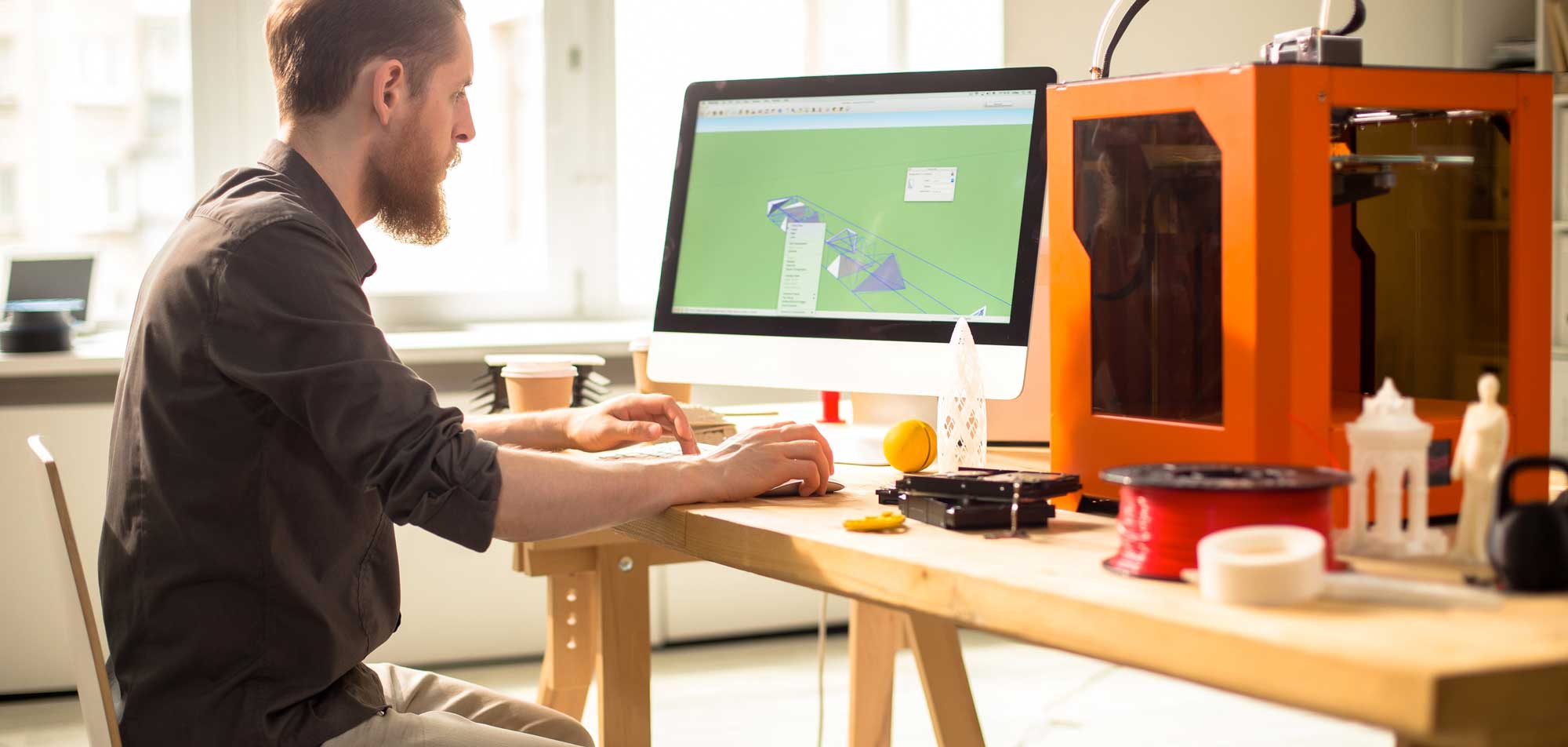 Справа — FDM 3D принтер, катушка с материалом и пара 3D распечатков