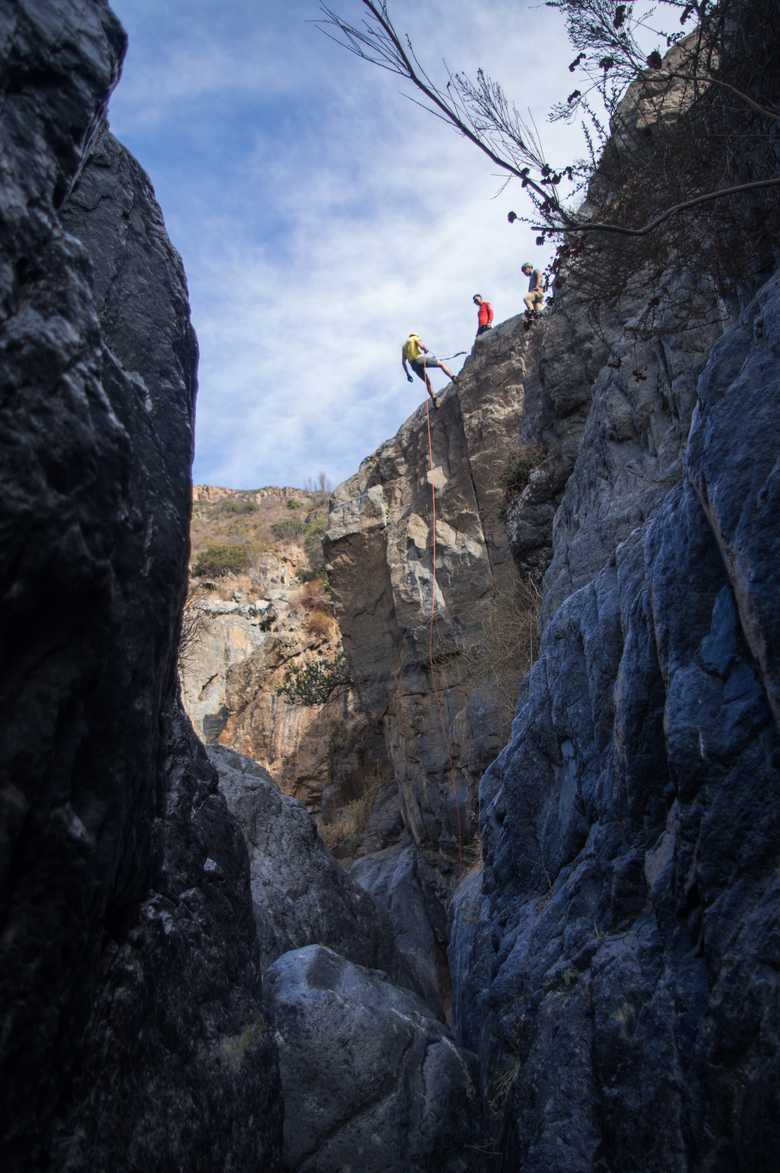 Sebastian [yellow] comfortably begins his second rappel. The nervous excitement that previously hung in the air quickly dissipated.