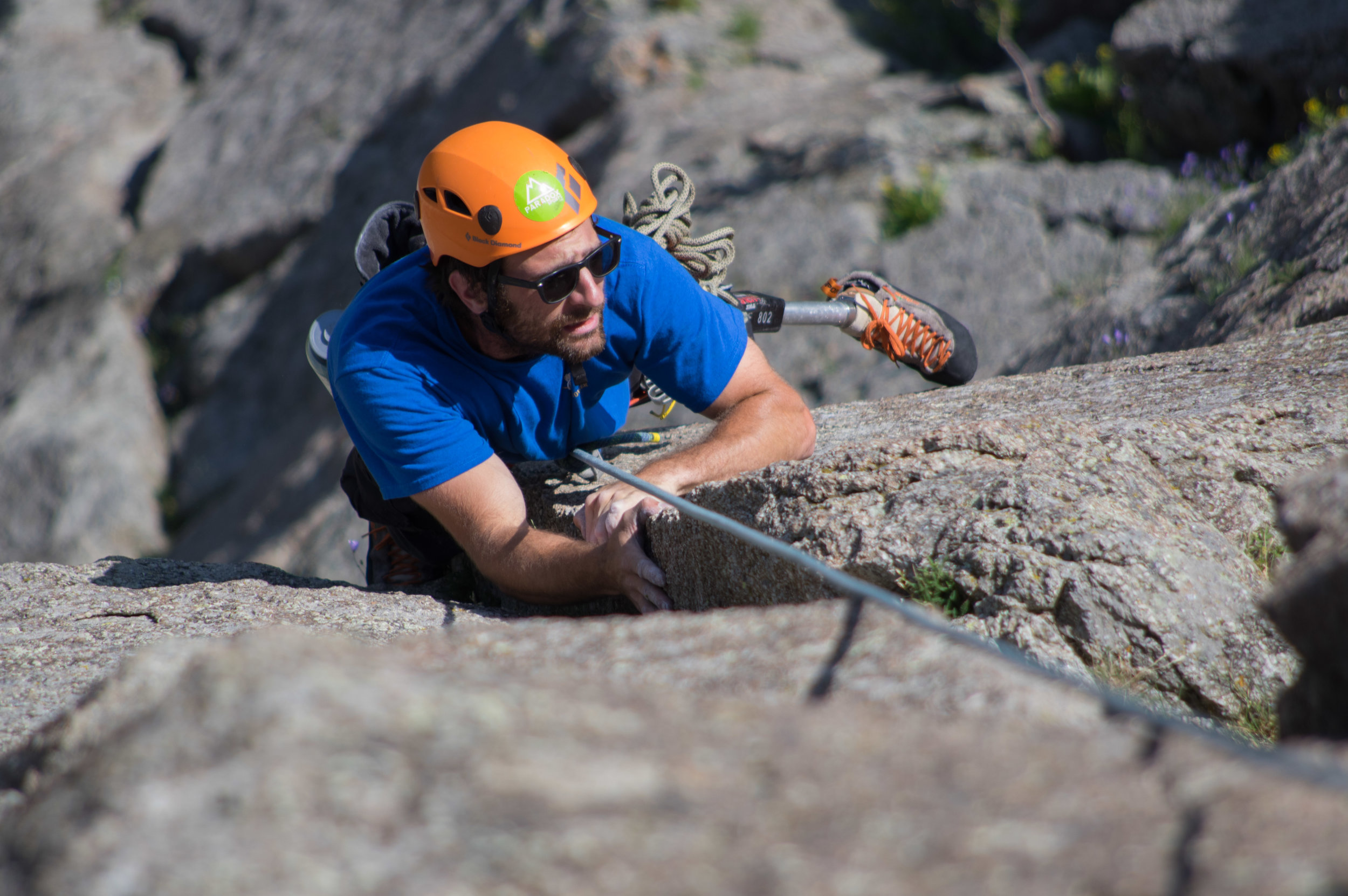 """The crux move of """"New Wave"""" (5.10a) Dave manages to find a foothold on an almost smooth rock column face."""