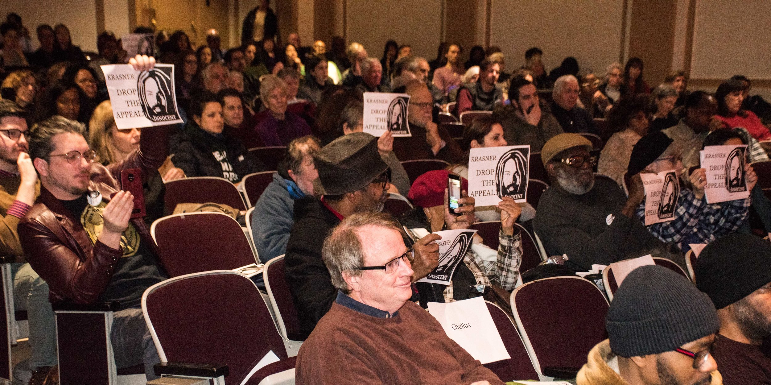 "2.11.19 Philadelphia - Mumia supporters hold up ""Krasner, Drop the Appeal"" posters as the phila. DA Larry Krasner speaks at a Criminal Justice Reform Panel at the Philadelphia Main Library."
