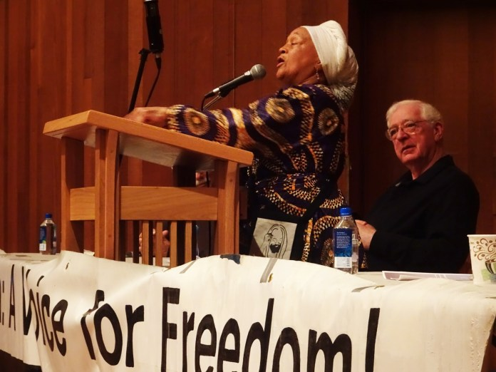 Pam Africa, famed for her fearlessness, inspires the crowd to deepen and broaden support for Mumia, as Jeff Mackler listens. – Photo: Wanda Sabir , SF BayView