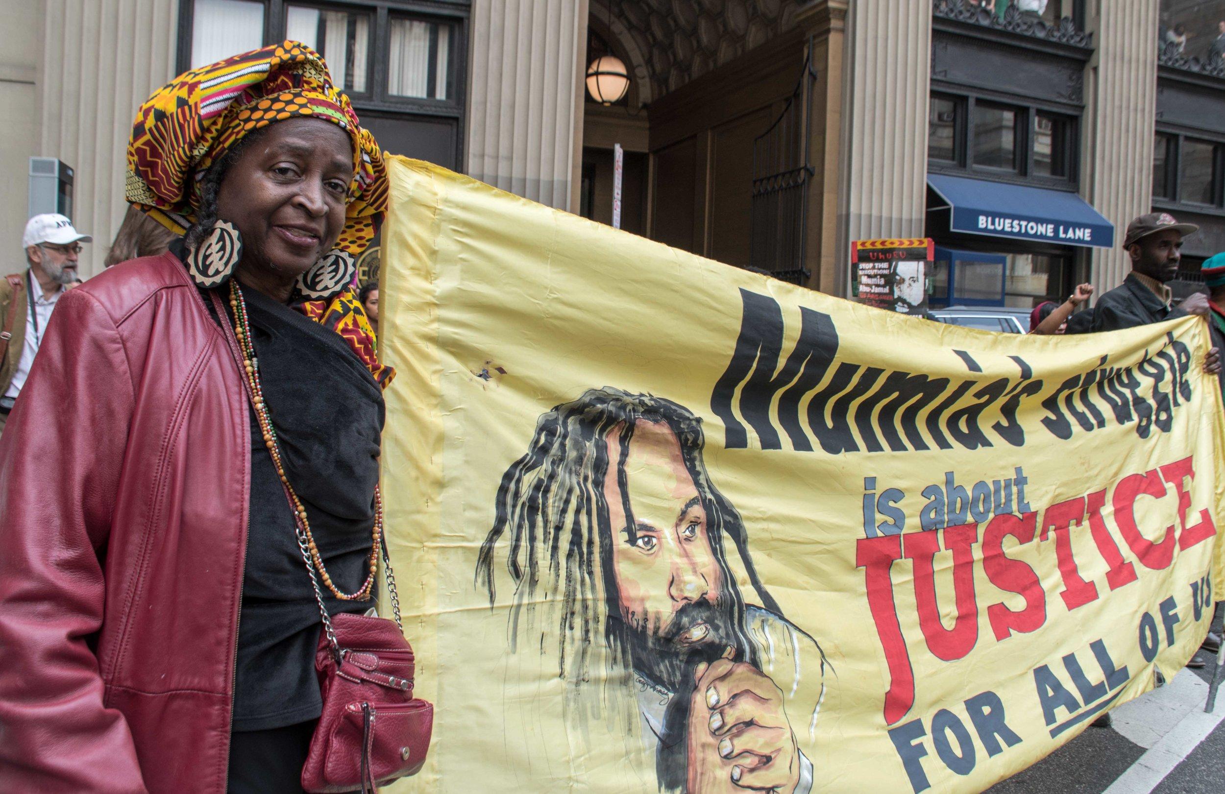 Philadelphia, Apr 18, 2019 - Press Conference for Mumia Abu-Jamal. Nana Njinga with banner. (photo credit: Joe Piette)