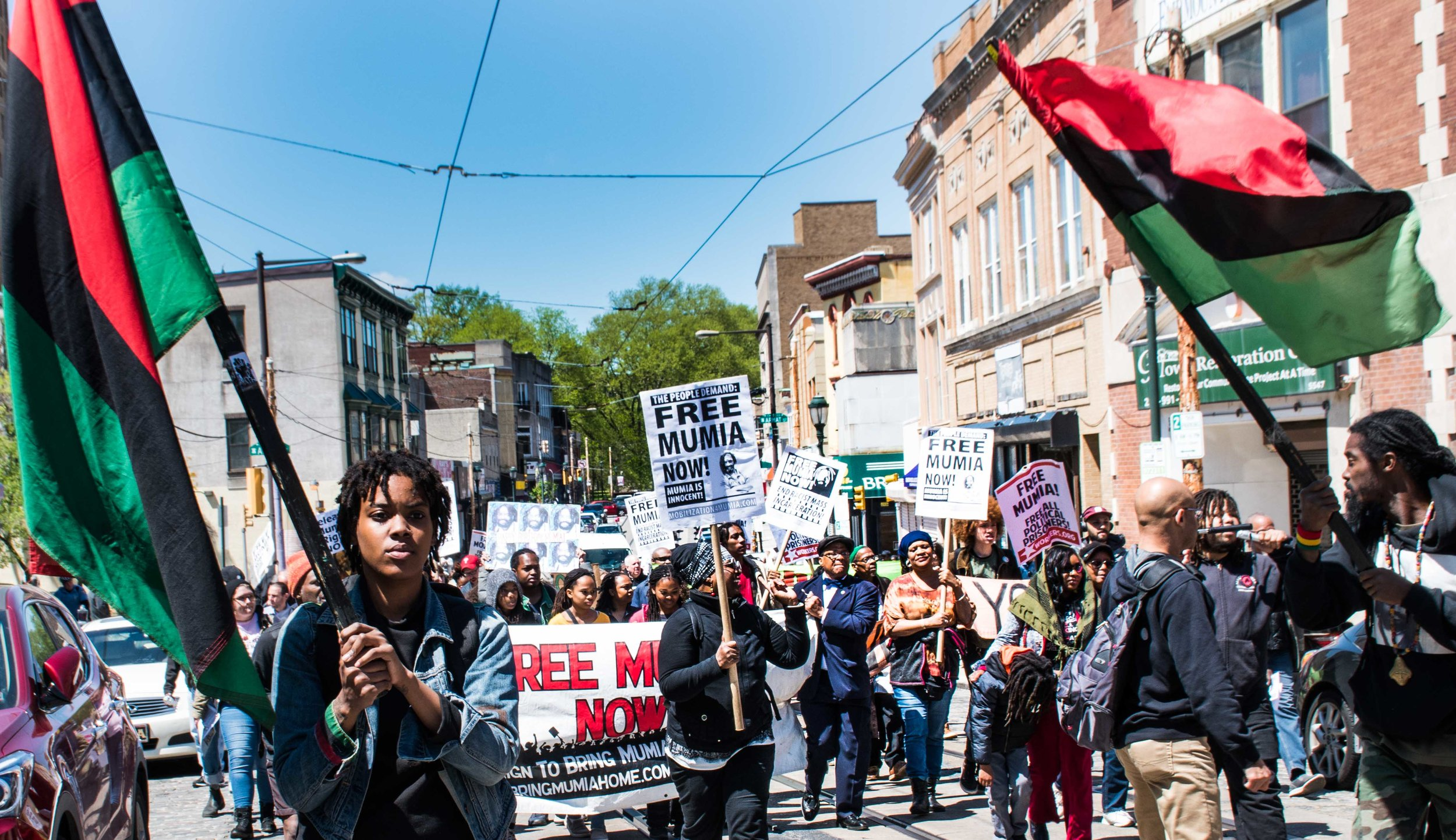 """Brick by Brick, wall by wall, we're going to free Mumia Abu-Jamal"" the chant on Germantown Ave April 27.  Photo credit - Joe Piette"