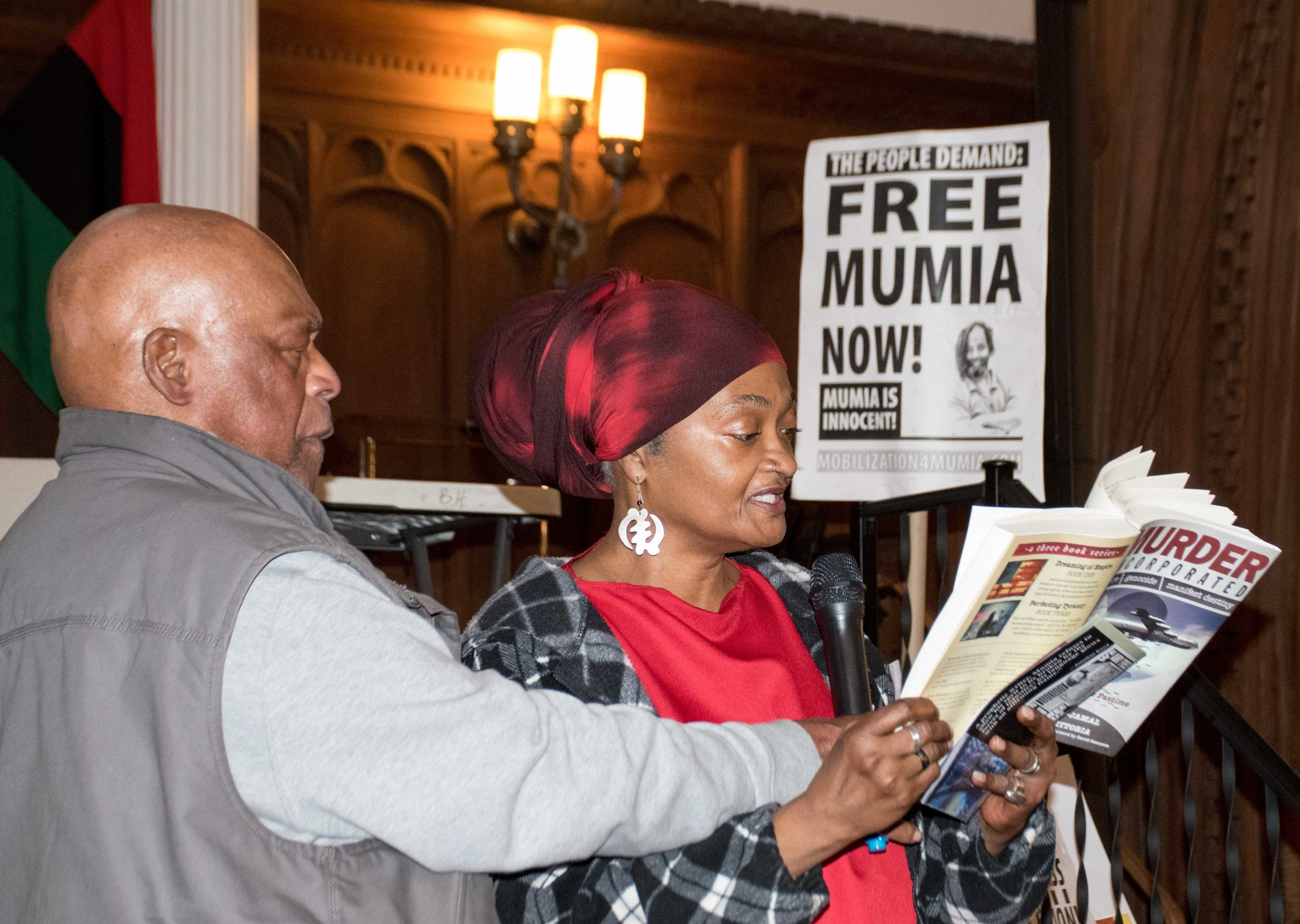 Fatirah Aziz reading from Mumia's new book at People's Sanctuary on April 27. (Mic is being held by Ralph Poynter.)  Photo credit - Joe Piette