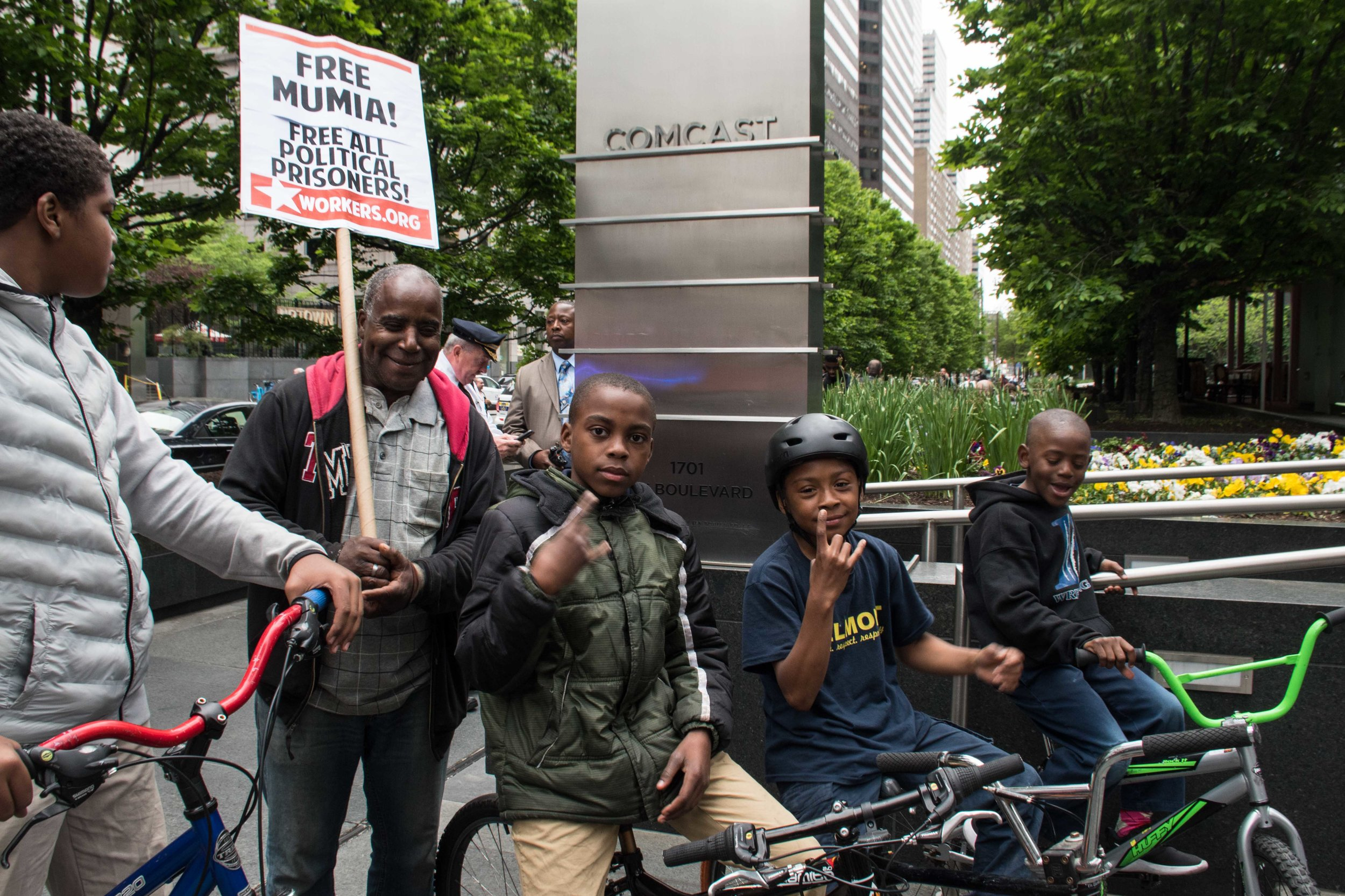 Young bikers express their solidarity as May 1st International Workers Day marchers stop at Comcast to protest against their anti-Immigrant policies. Photo credit: Joe Piette