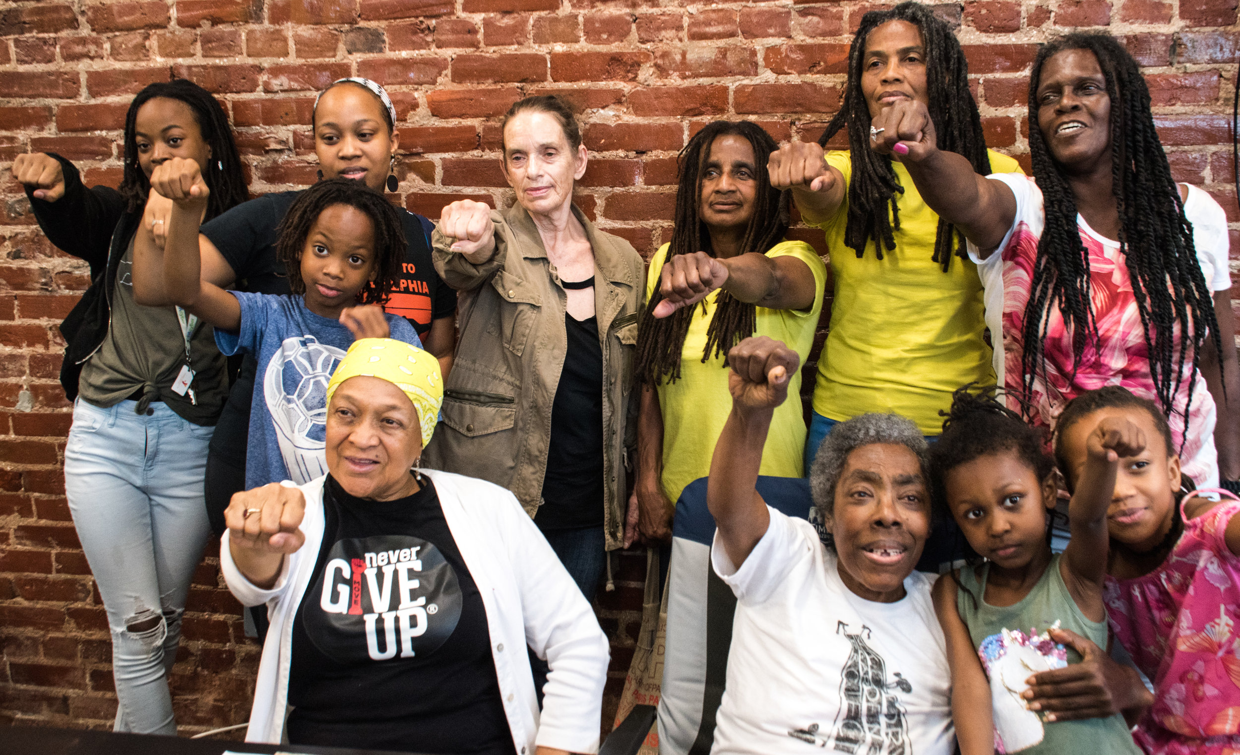 Newly released MOVE 9 members Janet and Janine Africa (in yellow shirts, L to R) with other MOVE members after May 30 press conference in Philadelphia. Photo; Joe Piette