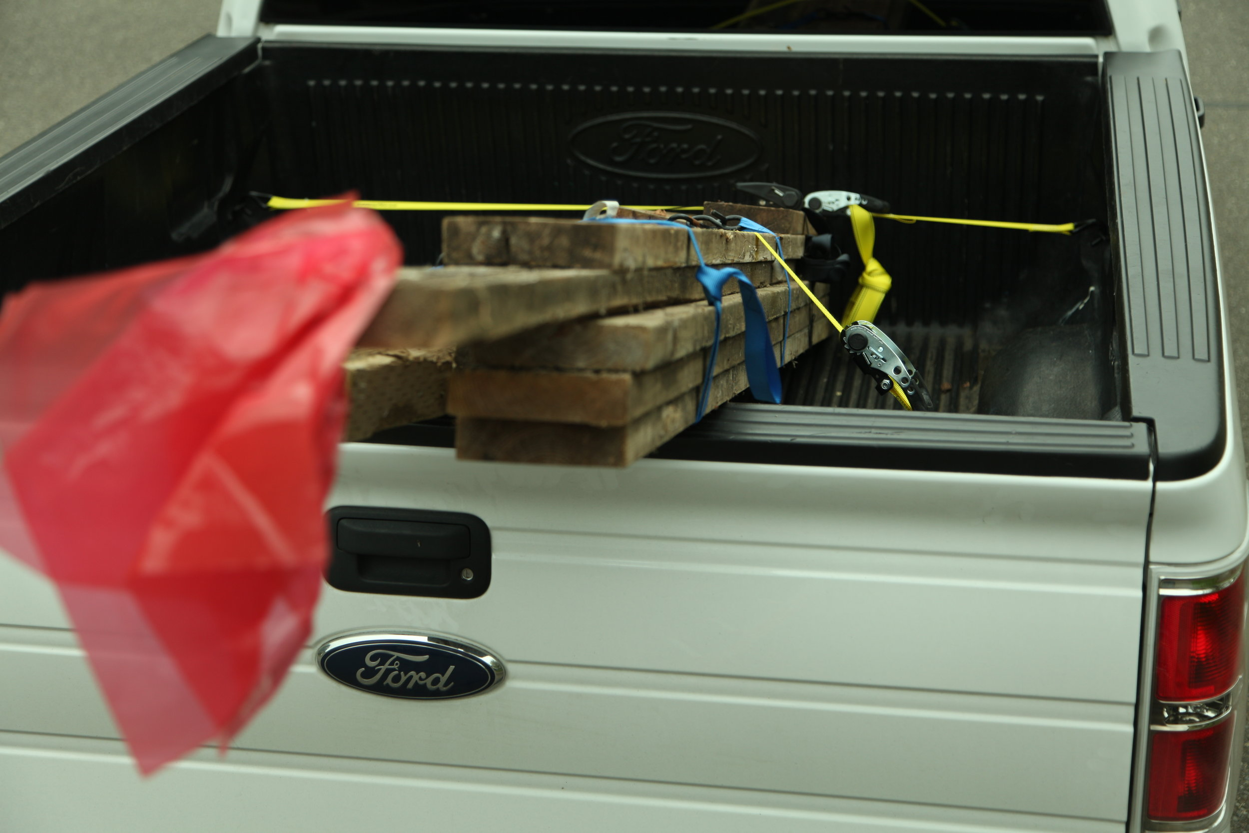 All corners of a load should be tagged with red flags (one foot by one foot), if the load extends four feet beyond the bed of a truck or trailer.
