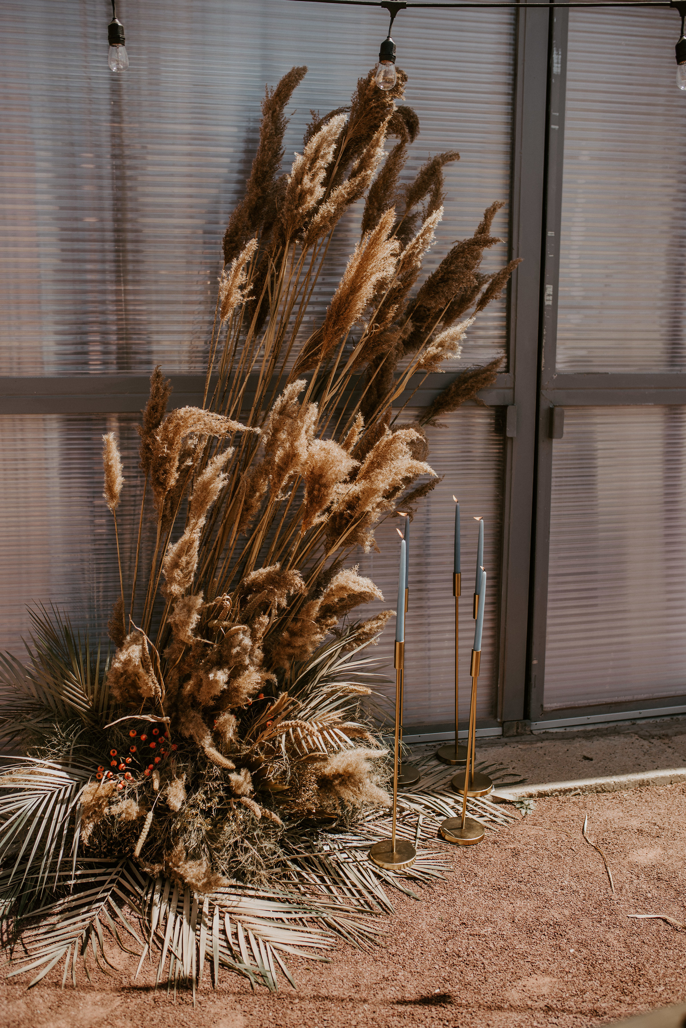 Amazing textural dried grasses and palm leaves by Studio Terrain with tall pale blue tapered candles helped create a romantic ambiance.
