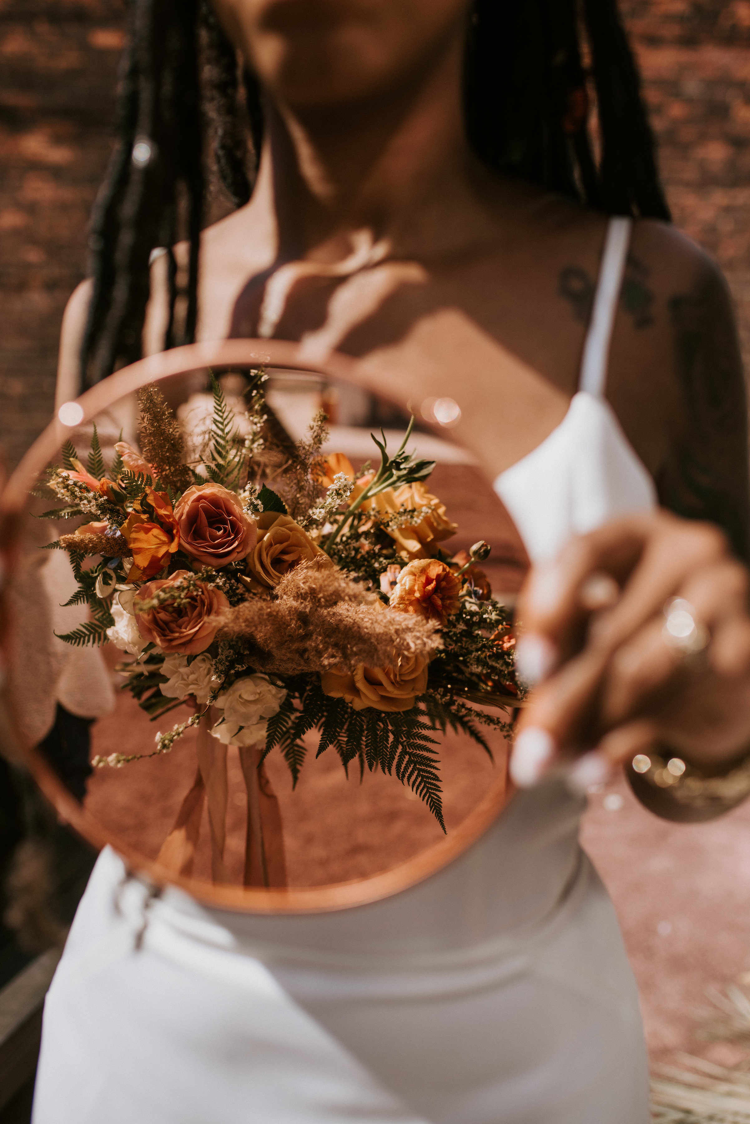 """l love this beautiful and creative shot of the bouquet by Northern Native Photography. The warm autumnal tones of the flowers Fatima of Studio Terrain designed went so well with Rosemarine Textiles 2"""" wide rust chiffon and 2"""" wide sand habotai silk ribbons."""