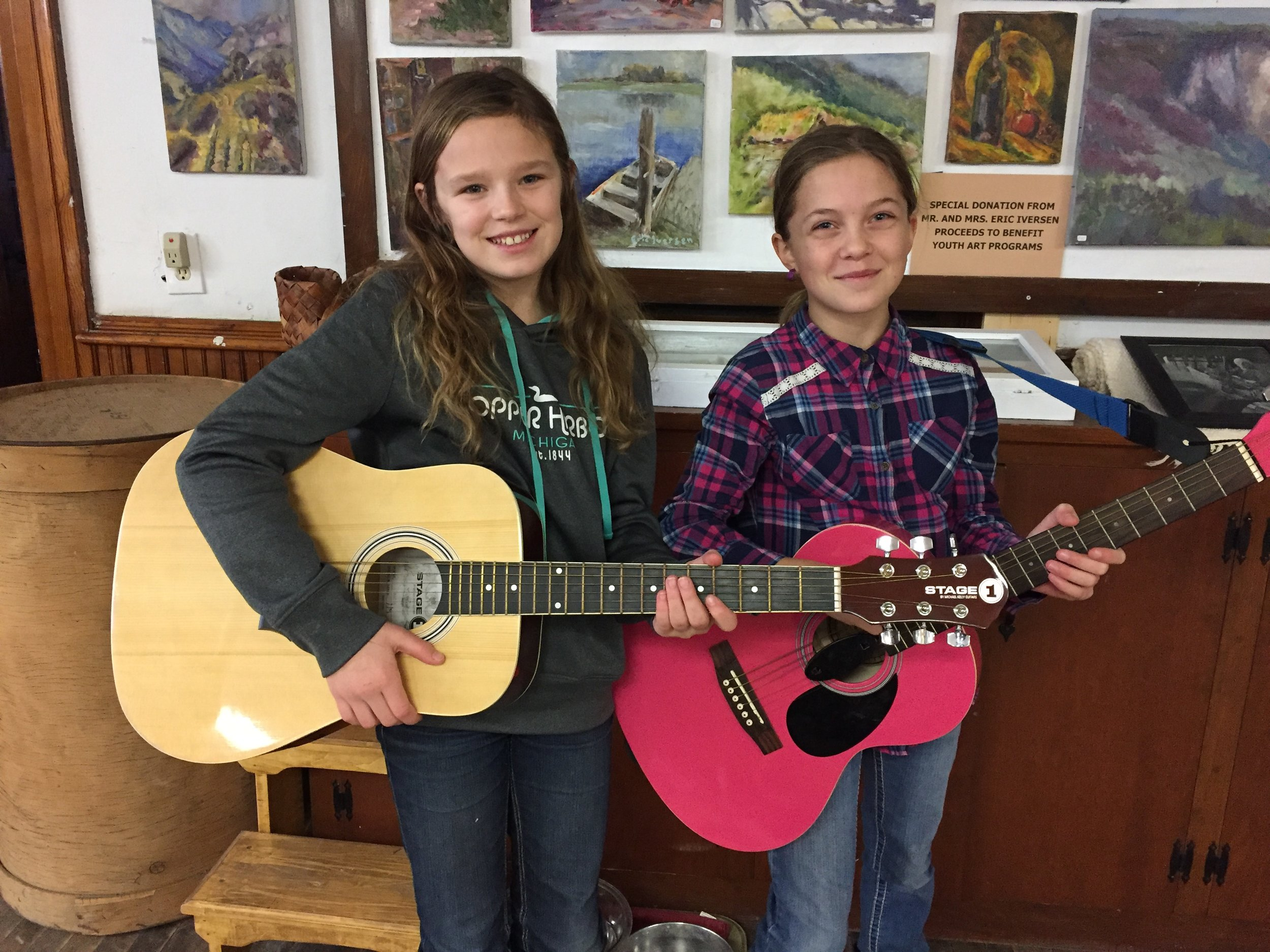 Two happy Gift of Music students with their new guitars