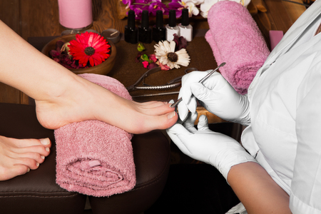 57242935_S_pedicure_nail_salon_feet_toes_tools_hygiene_woman_polish_towel.jpg