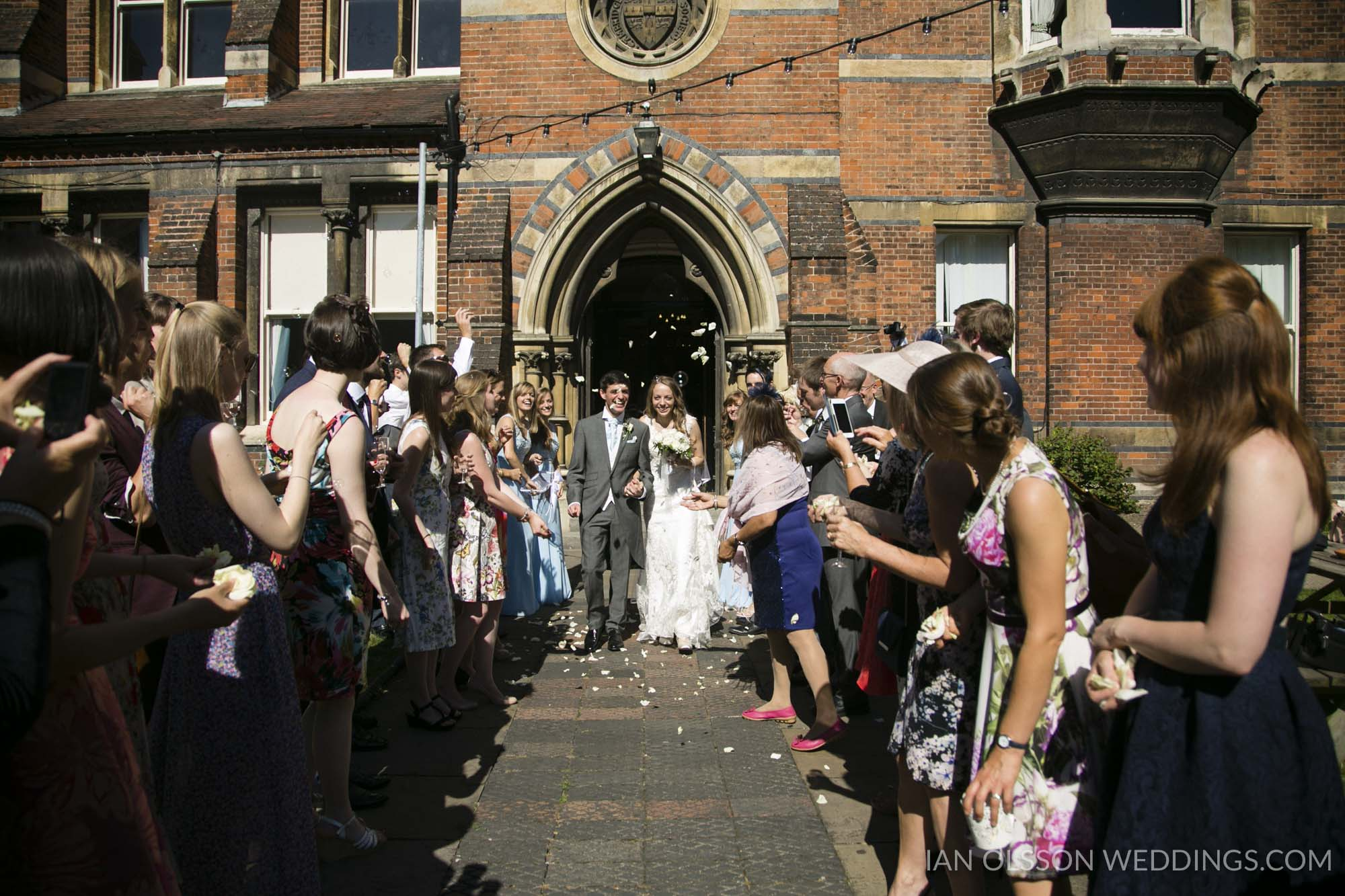 Arriving at the Cambridge Union through a confetti tunnel for their beautiful summer wedding reception