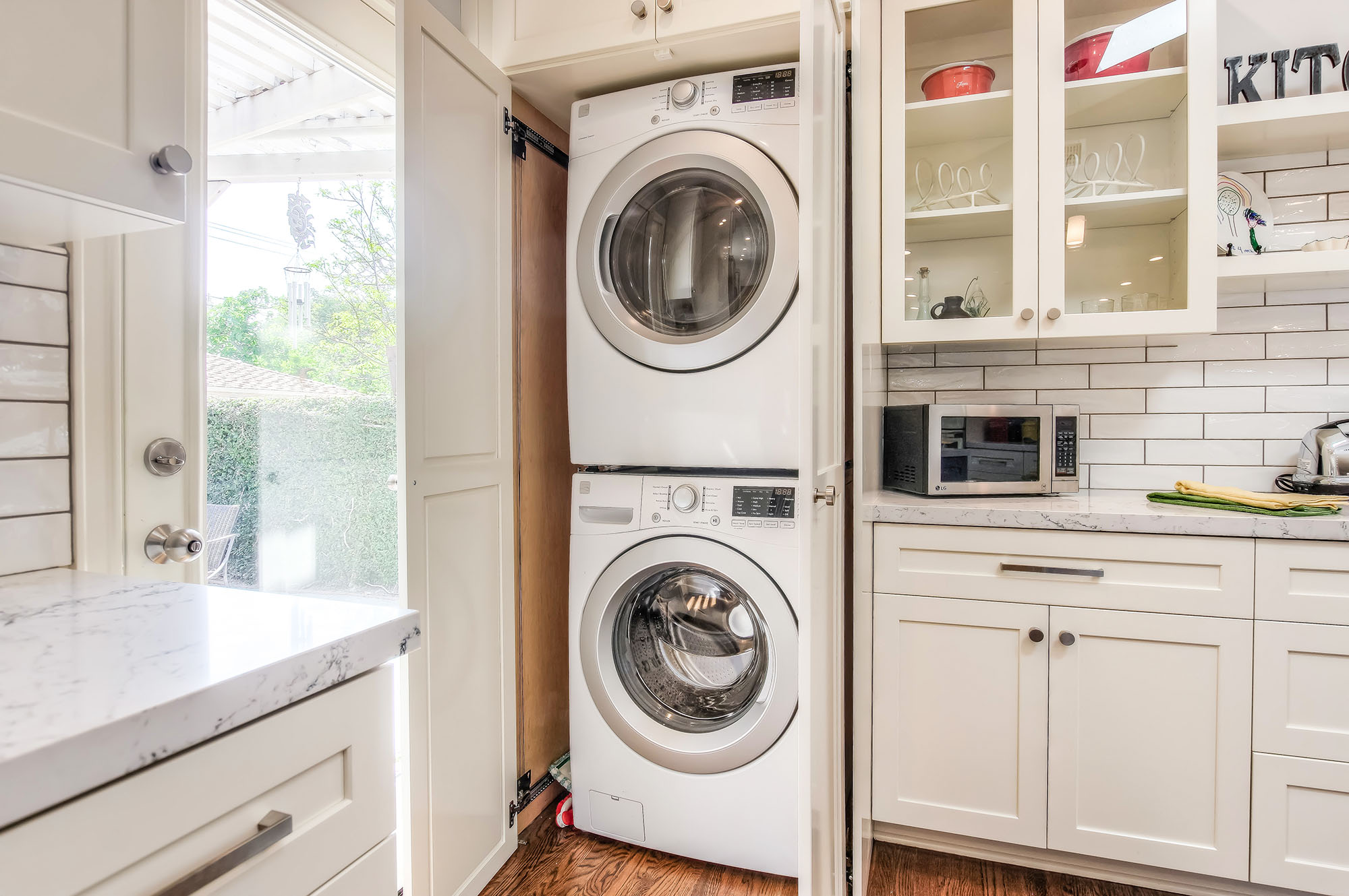 The kitchen includes a custom built cabinet for the washer and dryer extra storage for all laundry needs.