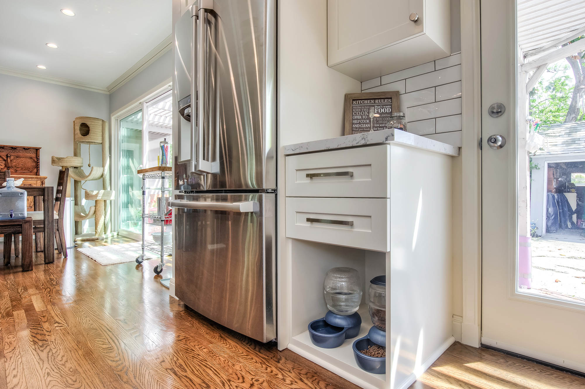The kitchen was designed with the client's pets in mind to create a covered space for their food and water and extra storage space for their toys, food and treats with their own separate cabinets.