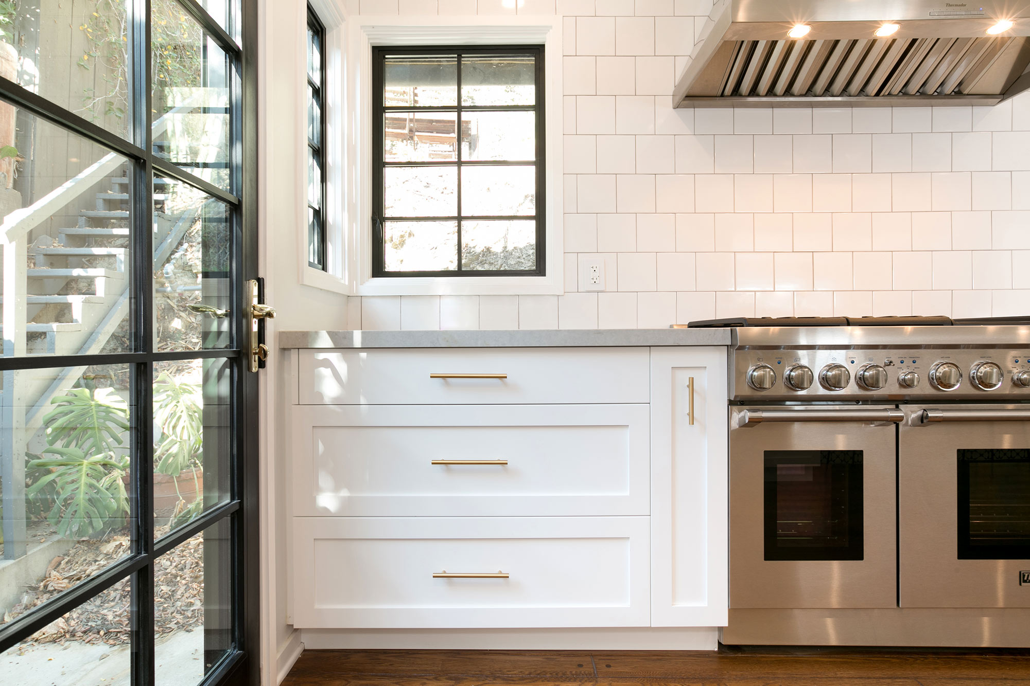 "The new open kitchen features custom-made white shaker cabinets with gold pulls and knobs, black fixtures, new hardwood floors, white 5""X5"" ceramic tile backsplash, Caesarstone Noble Grey countertops, breakfast bar with pattern cement tile detail, Thermador appliances and new wood clad windows painted black."