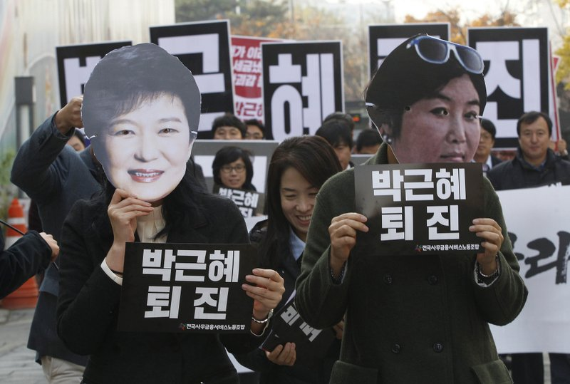 Protestors donned masks depicting President Park Geun-Hye and Choon Soonsil