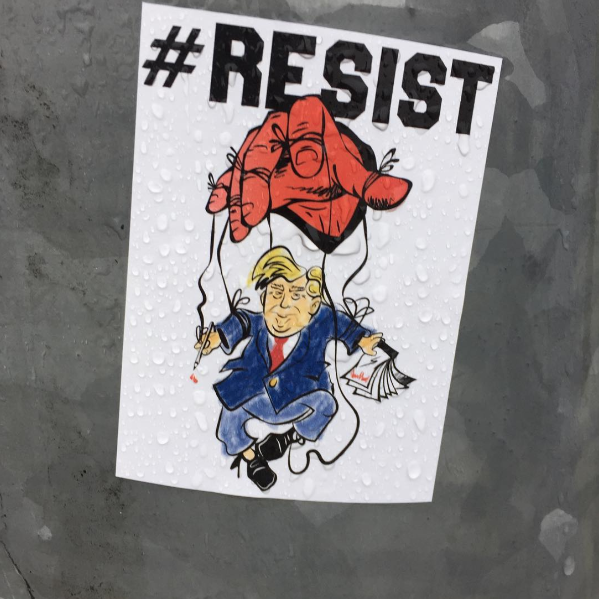 "Picture of President Trump as a marionette doll controlled by a red hand with the caption ""#RESIST"""