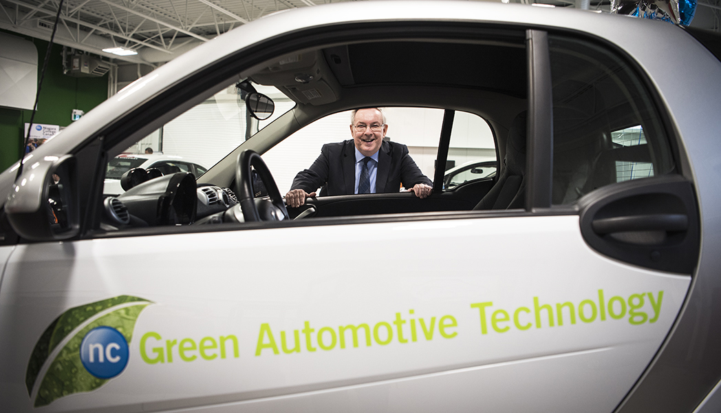 St. Catharines MPP Jim Bradley stands alongside one of the vehicles on display at Niagara College's Green Automotive Technology Lab during its grand opening in Welland, Ont.