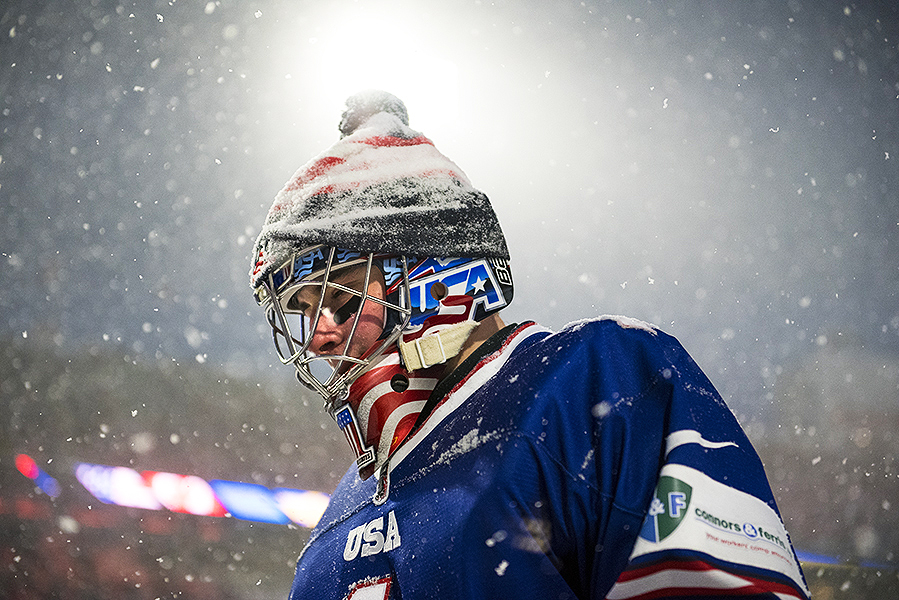 United States goaltender Jeremy Swayman is illuminated by the bright lights at Orchard Park, NY's New Era Field during the 2018 IIHF World Junior Championship's outdoor game.