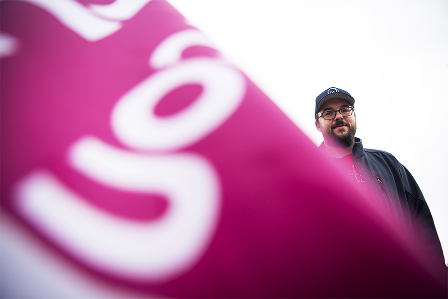 Kyle Hoskin, Unit Vice President for Emterra Environmental, is flanked by a CUPE flag. Dozens of protestors against Ontario Premier Doug Ford's minimum wage rollback gathered outside of the Ontario Economic Summit in Niagara-on-the-Lake, where Ford was speaking.