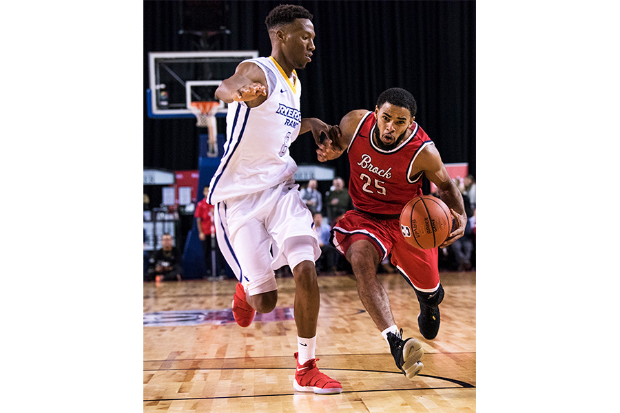 Brock University's Tyler Brown (#25) drives to the basket despite strong defence from Ryerson University's Jean-Victor Mukama (#8).
