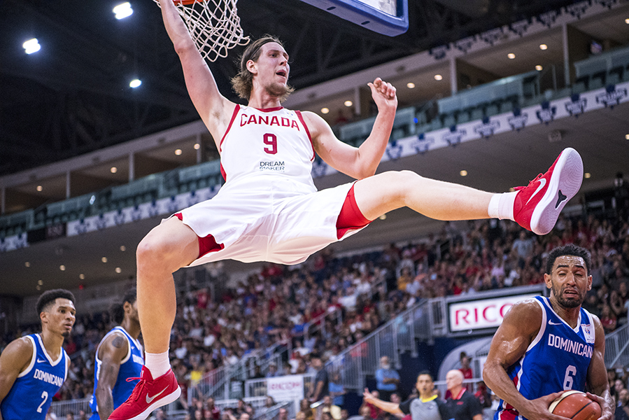 Team Canada's Kelly Olynyk (#9) hangs from the rim after a dunk against the Dominican Republic.