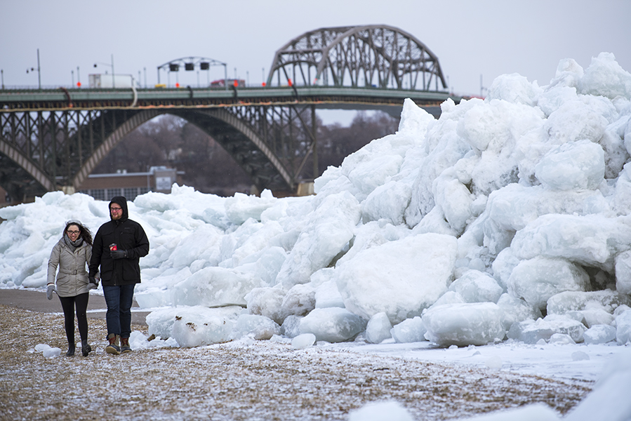 A couple walks alongside a large build up of ice at the shore of Mather Park in Fort Erie, Ont.