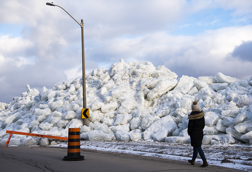A woman walks alongside a large build up of ice that pushed its way over the Niagara River's retaining wall in Fort Erie.